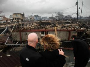 A couple looks at the devastation to their neighborhood after a fire caused by Sandy destroyed 80 homes.