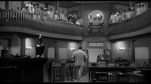 After the trial for Tom Robinson's life, attorney Atticus Finch leaves the courtroom in defeat.